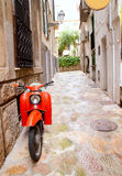 Mediterranean street with old retro red scooter Stock Photos