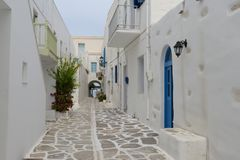 Mediterranean street with white houses and blue doors. Mediterranean street with white houses, blue doors and green tree in Paros Island, part of Cyclades, the Stock Photos
