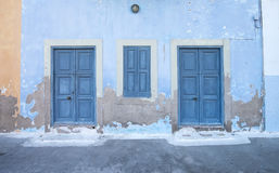 Mediterranean style exterior. Blue wooden doors. And window shutters on old painted wall on a Greek island of Kastelorizo Stock Photography