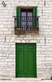 Mediterranean style facade. Closed door, window with open green shutters Royalty Free Stock Photo