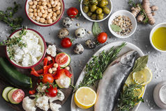 Mediterranean style food background. Fish, vegetables, herbs, chickpeas, olives, cheese on grey background, top view. Healthy food