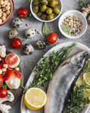 Mediterranean style food. Fish, vegetables, herbs, chickpeas, olives, cheese on grey background, top view. Healthy food concept.