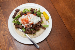 Mediterranean Style Lamb Gyro. A Gyro plate, Mediterranean style, made with seasoned lamb, lettuce, tomato, yogurt sauce and garnished with olives, and a banana stock photos