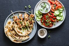 Mediterranean style lunch table - turkey skewers, flatbread, tomatoes, cucumber salad, baked sweet pepper, yogurt herb sauce  on a. Dark background, top royalty free stock images
