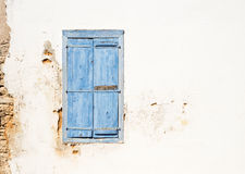Mediterranean style old window. Blue on light wall. Mediterranean style window. Blue on yellow wall with closed shutters Stock Image