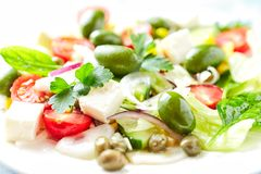 Mediterranean-style Salad with Green Olives, Feta Cheese, Cucumber, Cherry Tomatoes and Capers. royalty free stock photos