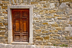 Mediterranean style wooden door on stone wall. Architecture detail view Royalty Free Stock Photography