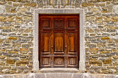 Mediterranean style wooden door on stone wall. Architecture detail view Royalty Free Stock Image