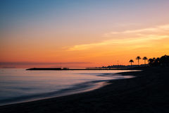 Mediterranean sunset in Marbella, Costa del Sol, Spain. Sunset at a beach in the Costa del Sol in Marbella, Spain, with the silhouette of a pier and Gibraltar to royalty free stock photography