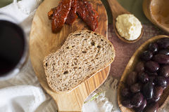 Mediterranean Tapas. Slice of fresh whole wheat bread with olives, hummus and sun dried tomatoes Royalty Free Stock Photo