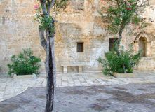 Church Yard, Village Square. Quiet, tranquil stone terrace area with trees and stone bench. Taken after a rain shower in the village of Mellieha on the Stock Images