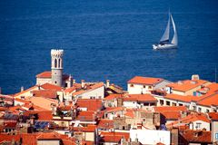 Mediterranean  town and a sailboat. Roofs of a typical Mediterranean  town and a sailing boat Royalty Free Stock Image