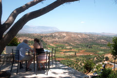 Mediterranean vacation. A couple take tea at a clifftop coffee-shop at Phaistos archaeological site, Crete, overlooking the olive groves of the Mesara Plain Stock Image