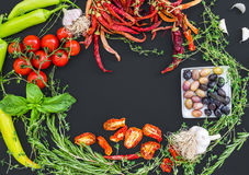 Mediterranean vegetable set consisting of garlic, chrry-tomatoes, dried tomatoes, fresh herbs, green and chili peppers and olives royalty free stock photography