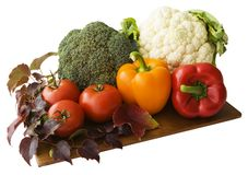 Mediterranean vegetables on a cutting board. Cauliflower, broccoli, tomatoes, red and orange peppers with some ornamental wine leaves - isolated on white stock photography
