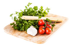 Mediterranean vegetables and spaghetti on white. A bunch of spaghetti, some cherry tomatoes, parsley and garlic on a cutting board isolated over a white Stock Photos