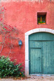 Mediterranean wall with door and window. A mediterranean style red wall with painted wooden door, small window and some climbing flowers Stock Photos