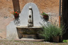 Mediterranean water fountain, lavender and geranium flower Stock Photo