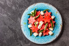 Mediterranean watermelon, feta cheese and mint salad on blue plate. Royalty Free Stock Images