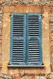 Rustic Mediterranean blue shutters in an ancient wall Stock Photo