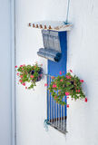 Mediterranean window. White facade: window with blue shutters and flowers on both sides royalty free stock image