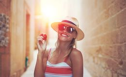 Mediterranean woman in hat holding tomato on street royalty free stock photo