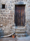 Mediterranean wood door and stone wall, Corsica. Wood door door and stone wall with a piece of wood lying next to it Stock Images