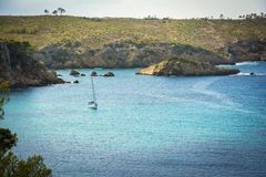 Sailing boat on blue mediterranean water in Ibiza island. Mediterraneans scene. Turquoise crystal clear waters of Ibiza island. Sailing boat on the water Royalty Free Stock Image