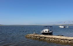 Mediterranian seaside view with small handmade pier and boats Royalty Free Stock Photo