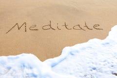 Meditieren Sie - geschrieben in den Sand Lizenzfreies Stockbild