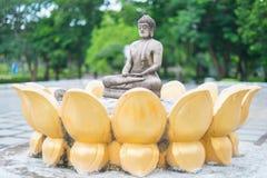 Meditierende Buddha-Steinstatue im Park thailand Stockfotos