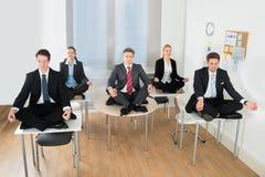 Meditierende Wirtschaftler, die auf Schreibtisch sitzen Stockbilder