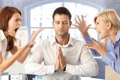 Meditierender Geschäftsmann mit der Argumentierung der Kollegen Stockfoto
