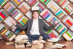 Meditierender Mann in der Bibliothek mit Büchern auf Kopf stockbilder