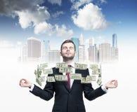 Meditierender Mann und fliegende Dollaranmerkungen zwischen seinen Händen Eine Skizze von New York City auf dem Hintergrund Stockfotografie
