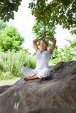 Meditierendes blondes Mädchen, das unter einem Baum auf einem Stein sich entspannt Stockfotografie