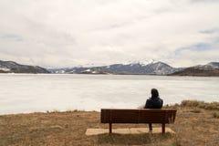 Meditierendes Sitzen der Frau vor gefrorenem und ruhigem See Dillon, Colorado stockfotos