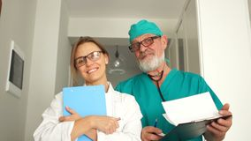 Mediuina and healthcare concept. Young female doctor and mature male doctor with a beard and a stethoscope are looking