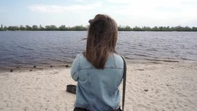 Medium back view of woman with beautiful hair on the shore stock video