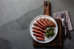 Medium beef steak on white plate, slate background Royalty Free Stock Photos