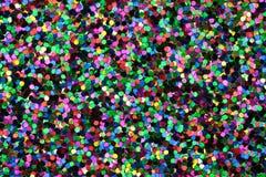 Medium Black/Green/Blue/Pink/Yellow Glitter. Macro photo of medium sized green, blue, pink, orange, black, and yellow glitter Royalty Free Stock Photo
