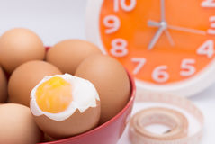 Medium-boiled eggs  in red bowl with clock for morning time conc Stock Photo