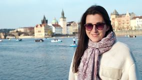 Medium close-up adorable young smiling woman posing on embankment of typical European city at sunset stock video