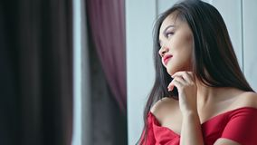 Medium close-up beautiful Asian woman wearing red dress smiling and looking on window stock footage