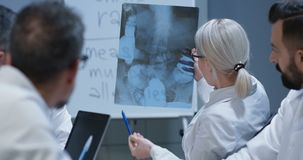 Doctors discussing bone injury diagnosis. Medium close-up of doctors discussing bone injury while analyzing x-ray image stock footage