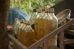Medium close up of gasoline bottles on a wooden rack in rural Cambodia Stock Photography