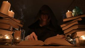 Medium close-up girl magician in a hood in a dark room by candlelight and looking for a spell turning over a book. Low. Key. Mystic Small DOF stock video footage