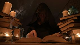 Medium close-up girl magician in a hood in a dark room by candlelight and looking for a spell turning over a book. Low. Key. Mystic Small DOF stock footage