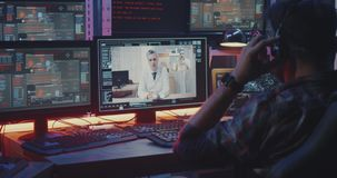 Hacker intercepting doctors video call. Medium close-up of a hacker intercepting a video call between two doctors stock video footage