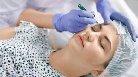 Specialist of permanent make-up create shape of eyebrows using tweezers